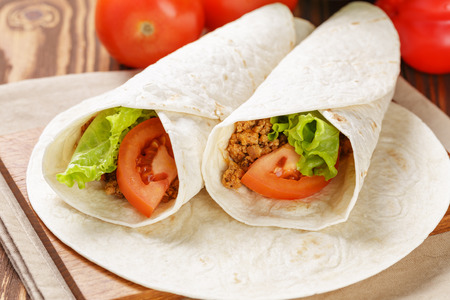 burritos with beef tomato and salad leaf on old wooden table rustic style photo