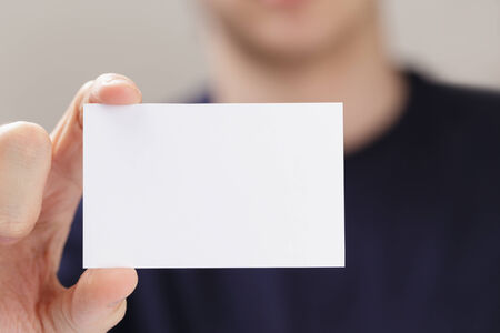 adult man hand holding empty business card in front of camera, blurred background photo