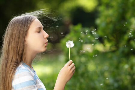 teenage girl blowing a dandelion, against natural background photo