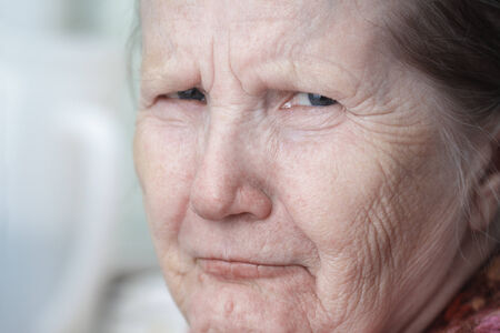 tough looking old woman, close up portrait photo