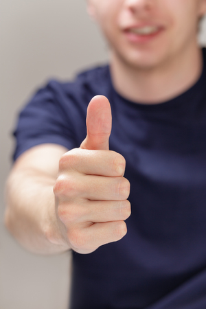 adult man shows thumb up, blurred background photo