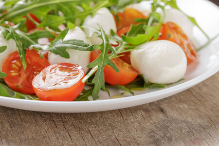 salad from arugula tomatos and baby mozzarella, on wood table photo