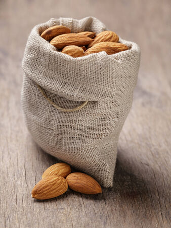 small sack bag full of almonds, on wooden table photo