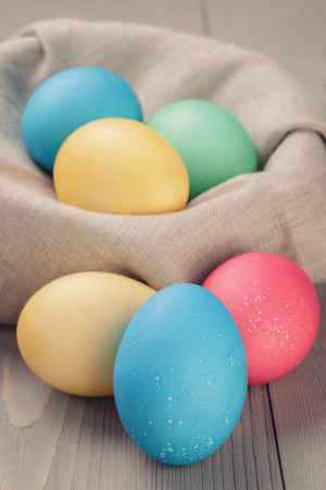 easter eggs in nest from sack textile rustic style, vintage toned photo