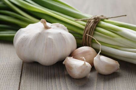 spring onion: bunch of fresh green onions and garlic, rustic style Stock Photo