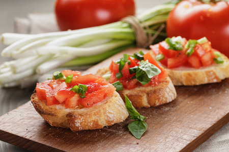 topped: simple italian appetizing bruschetta with tomato, on old table Stock Photo
