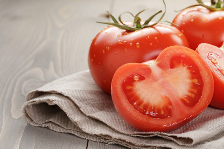 fresh ripe tomatoes with halfs on wood table, rustic style