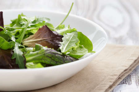 mesclun mix salad in white bowl on wood table photo