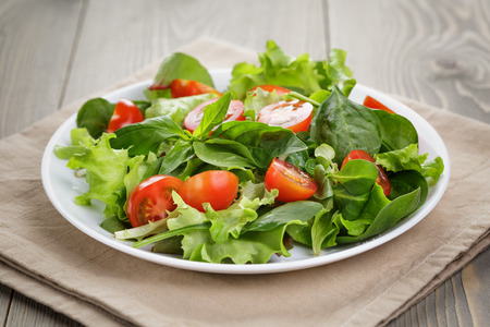 summer salad with tomatoes in white plate on wood table