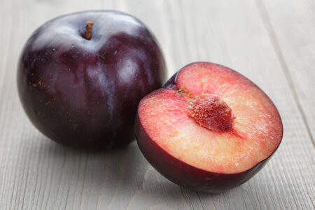 black plums on rustic table, wood surface photo