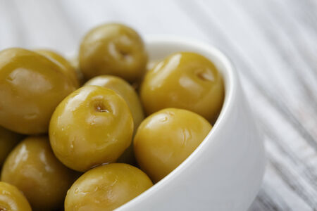 green salted olives in white bowl, on wooden table photo