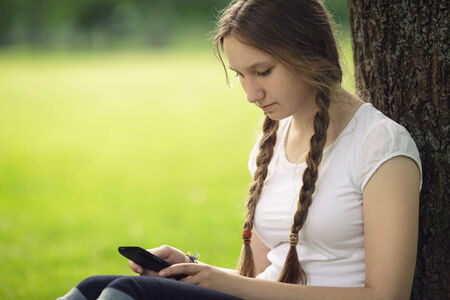 teen girl sitting near tree with mobile phone outdoors in park photo