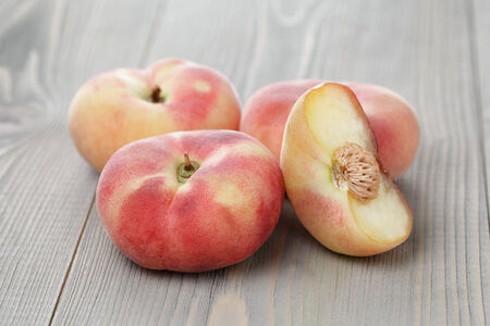 flat peaches on wood table, simple rustic style photo