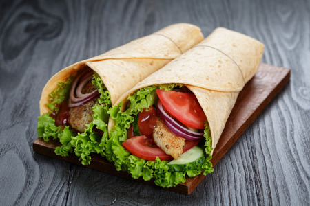 pair of fresh juicy wrap sandwiches with chicken and vegetables, on black wood table