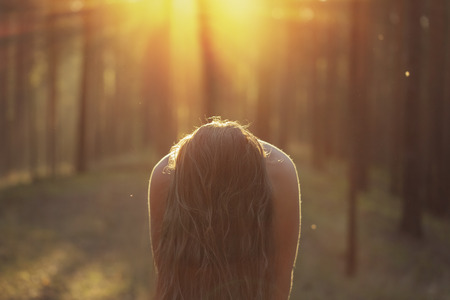 girl with long hair closing face in moody forest, sunset photo