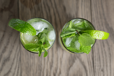 two mojito cocktails on old oak table, rustic style photo