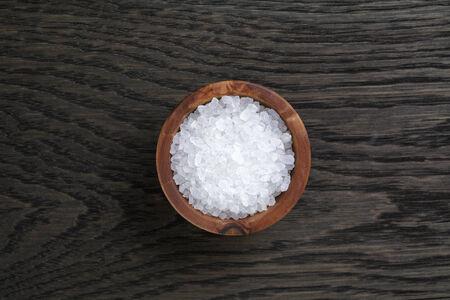 salt: la sal del mar en un taz�n de madera para la cocina o el spa, en la mesa de roble oscuro