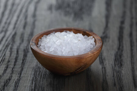 sea salt in wooden bowl for cooking or spa, on dark oak table photo