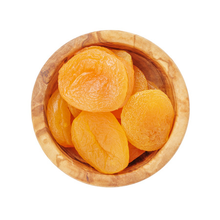 apricots: heap of dried apricots in wood bowl from above, isolated on white background Stock Photo
