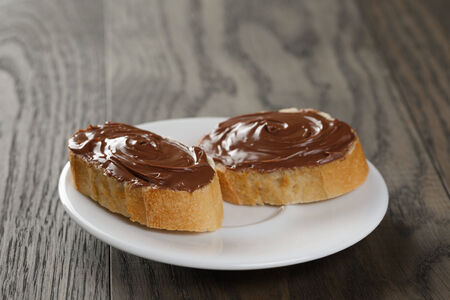 two paguette slices with cocoa nut spread, on wood table photo