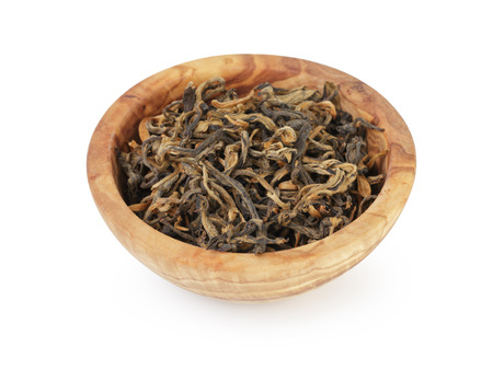 heap of famous dian hong yunnan tea in bowl, isolated on white photo