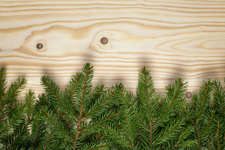 border from fir twigs on wood background, christmas backdrop photo