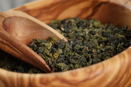 oolong green tea in wood bowl, on oak table 스톡 콘텐츠