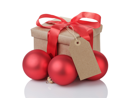 wraped gift box with red bow, christmas balls and tag, isolated on white