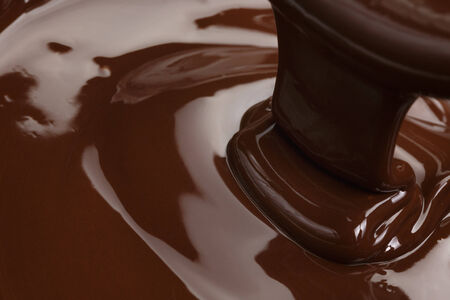 melted dark chocolate flow, candy or chocolate preparation background photo