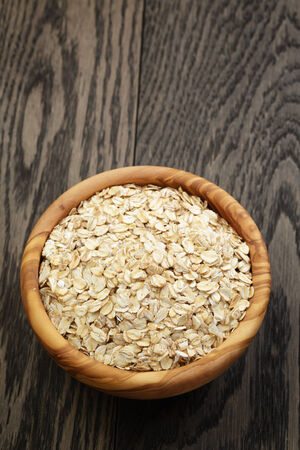oat flakes in wood bowl on oak table, rustic style photo