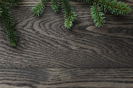 view from above: fir branch on stained oak table from above, christmas background