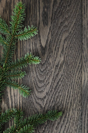 fir branch on stained oak table from above, christmas background photo