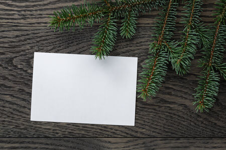 fir branch with paper card on oak table from above, christmas background photo