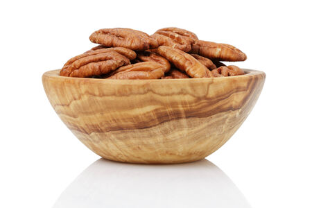 pekan: pekan nuts in wood bowl, isolated on white background