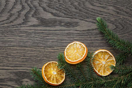 spruce twig with dried orange slices on oak table, christmas background photo