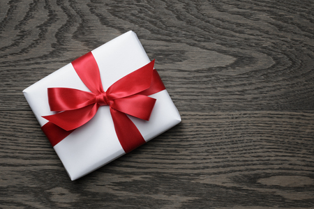 wrapped gift: gift box with red bow on wood table, top view Stock Photo