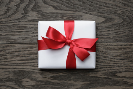 gift box with red bow on wood table, top view Stockfoto