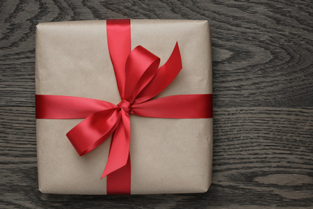 brown gift box with red bow on wood table, top view 写真素材