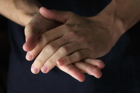 manos orando: adultos manos del hombre abrochadas, foto estilo oscuro