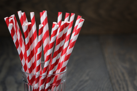 vintage paper straws in glass on wood table, rustic style