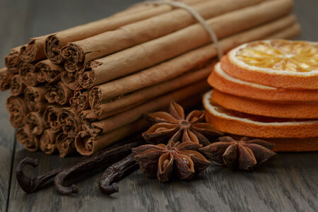cinnamomum: true cinnamon sticks and dried oranges, on rustic oak table