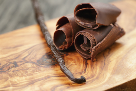three peeled chocolate curls on olive wood board, closeup photo