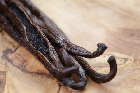 open vanilla pod on olive board, close up photo Stock Photo