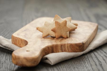 galletas de jengibre: homemade star shape ginger cookies on olive board, rustic photo Foto de archivo