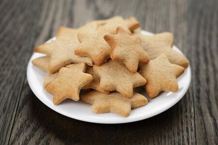 galletas de jengibre: galletas caseras en forma de estrella de jengibre en la mesa de madera, foto r�stica
