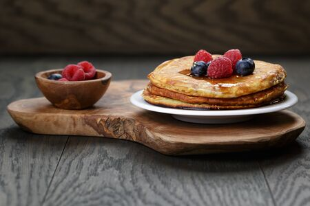 Pancakes with raspberry, blueberry and maple syrup, on oak wooden table photo