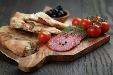 Antipasti with salami, olives, tomatoes and bread on wod table photo