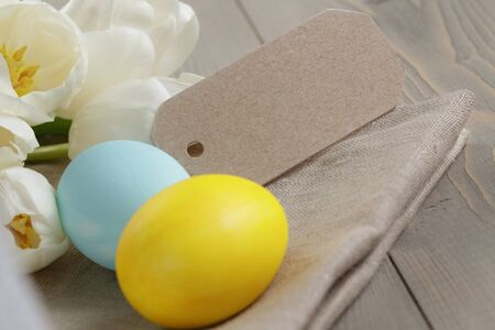 easter eggs and white tulips on wood table, paper card for text photo