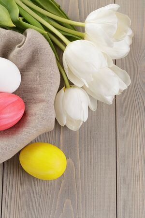 easter eggs and white tulips on wood table photo