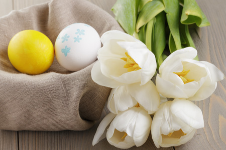 handpainted easter eggs and white tulips on wood table photo